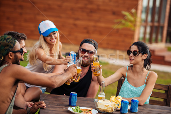 Teenage friends sitting at table and having fun outdoors Stock photo © deandrobot