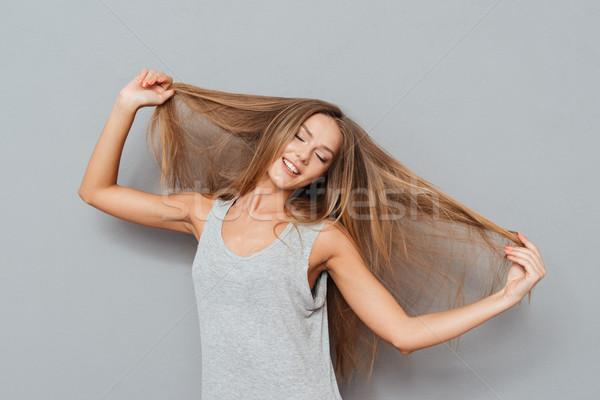 Souriant jeune femme cheveux longs posant isolé Photo stock © deandrobot