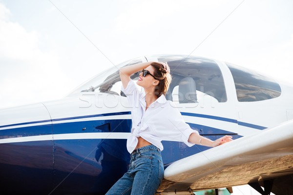 Happy woman standing near private plane Stock photo © deandrobot
