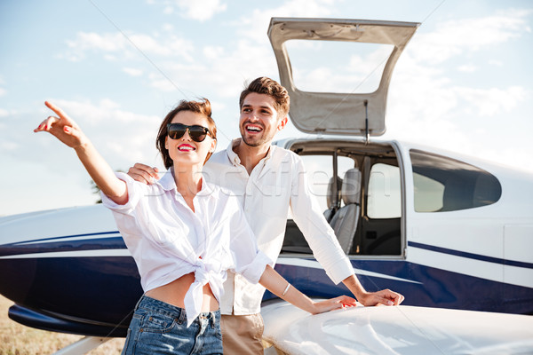 Couple standing near small plane and pointing away Stock photo © deandrobot