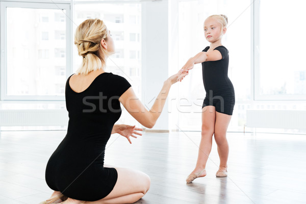 Ballet instructor directing little cute ballerina during dance practice Stock photo © deandrobot