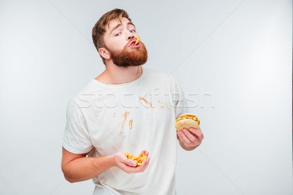 Happy bearded man enjoying eating hamburgers Stock photo © deandrobot