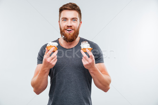 Cheerful smiling bearded man eating cream cake Stock photo © deandrobot