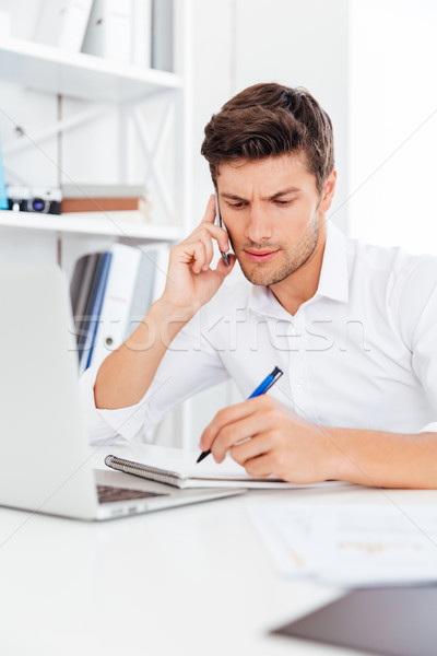Stock photo: Businessman talking on the mobile phone and making notes
