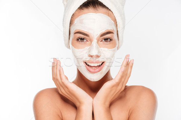 Beautiful smiling woman with white clay facial mask on face Stock photo © deandrobot