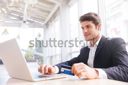Businessman using laptop and credit card in office Stock photo © deandrobot