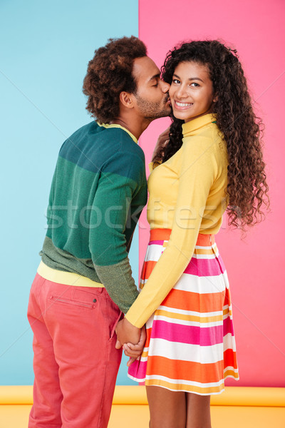 Happy african young couple kissing and holding hands Stock photo © deandrobot