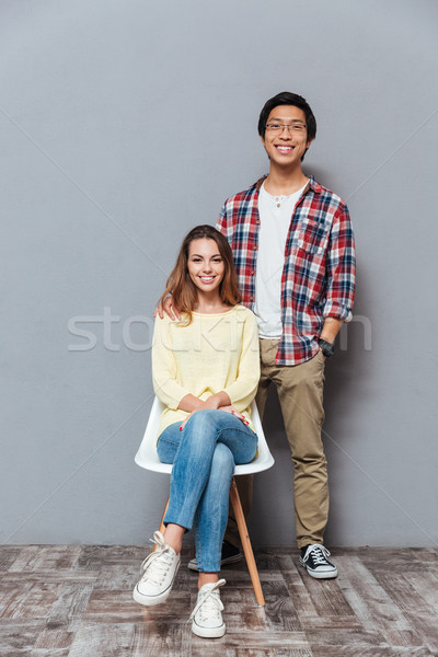 Full length portrait of a interracial couple standing and sitting Stock photo © deandrobot