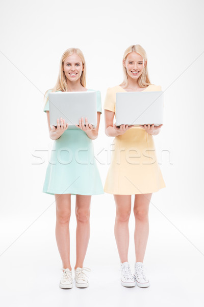 Two ladies looking at the camera and holding laptops Stock photo © deandrobot