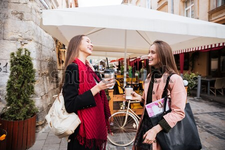 Two cheerful women with takeaway coffee walking in old town Stock photo © deandrobot