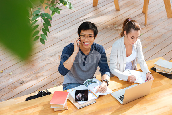 Dois estudantes estudar falante celular café Foto stock © deandrobot