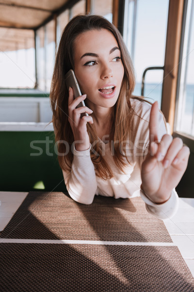 Vertical image Woman talking at phone on date in cafe Stock photo © deandrobot