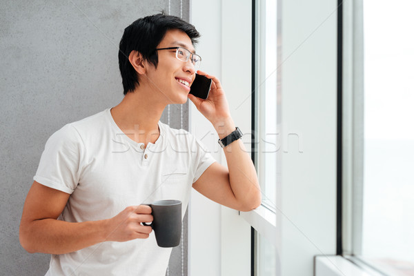 Asian man with coffee near the window Stock photo © deandrobot
