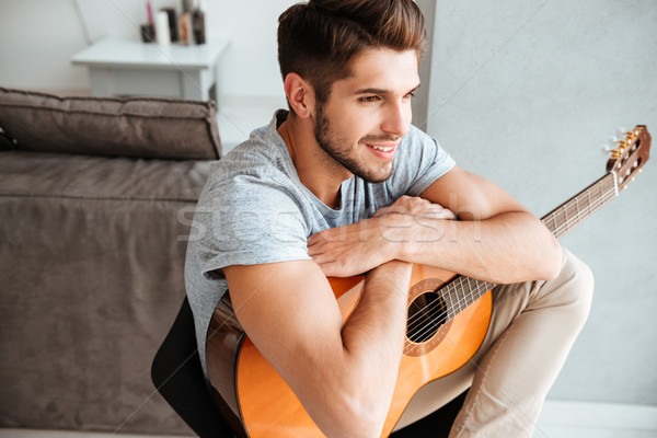 Happy man sitting with guitar on chair and look aside Stock photo © deandrobot