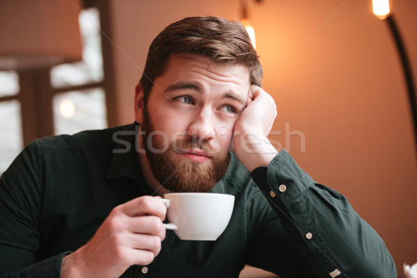 Sad bearded young man drinking coffee. Stock photo © deandrobot