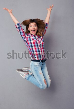 Full length of cheerful little girl standing with raised hands Stock photo © deandrobot