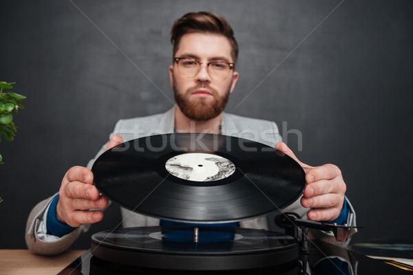 Serious young man in glasses using turntable and vinyl record Stock photo © deandrobot