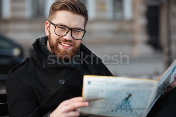 Cheerful bearded young man in glasses reading newspaper outdoors Stock photo © deandrobot