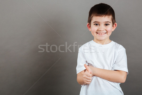 Smiling little boy standing and showing thumbs up Stock photo © deandrobot