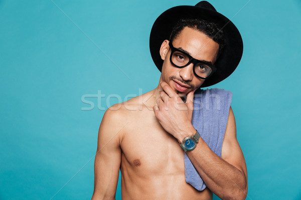 Young casual shirtless african man in hat and eyeglasses thinking Stock photo © deandrobot