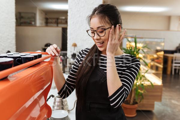 Asian barmaid near the coffee maker Stock photo © deandrobot