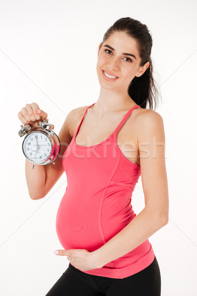 Smiling lovely pregnant woman holding alarm clock Stock photo © deandrobot
