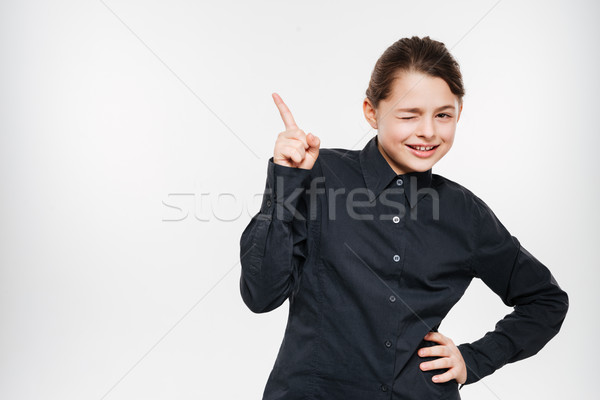 Happy young girl posing and pointing Stock photo © deandrobot