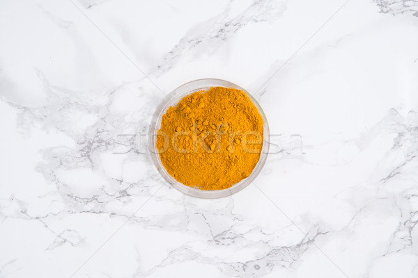 Top view of a turmeric powder in a bowl Stock photo © deandrobot