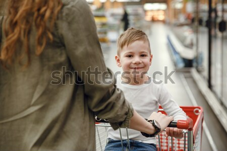 Happy young boy sitting in shopping trolley and looking camera Stock photo © deandrobot