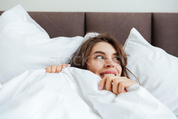 Alegre jovem senhora mentiras cama casa Foto stock © deandrobot