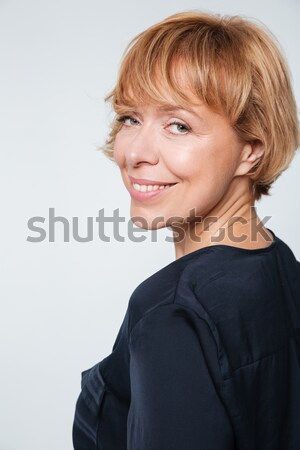 Close up image of smiling elderly woman standing sideways Stock photo © deandrobot