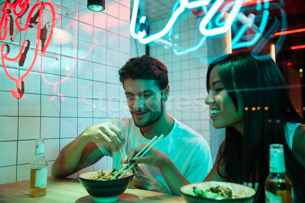 Multiethnic smiling loving couple sitting in cafe eating. Stock photo © deandrobot