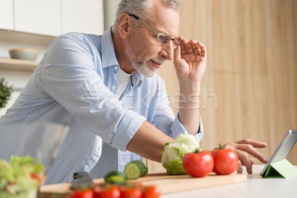 Przystojny dojrzały mężczyzna okulary gotowania Sałatka Zdjęcia stock © deandrobot