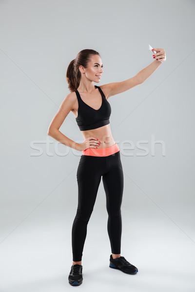 Full length image of smiling fitness woman making selfie Stock photo © deandrobot