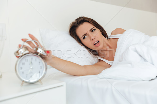 Irritated angry woman laying in bed Stock photo © deandrobot