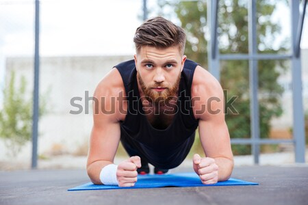Serious strong sportsman in gym make yoga sport exercises. Stock photo © deandrobot