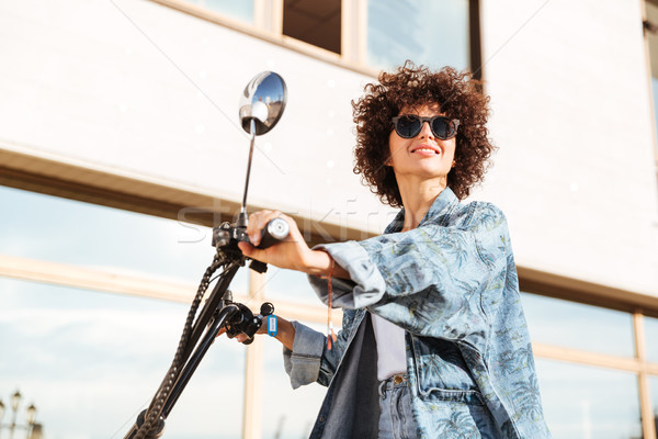 Side view of beauty smiling curly woman in sunglasses Stock photo © deandrobot