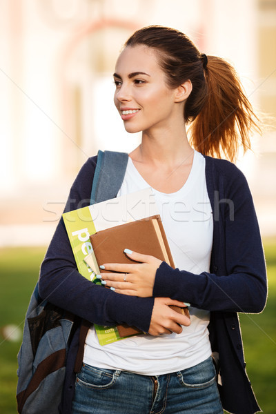 Portrait of an attractive smiling student girl standing Stock photo © deandrobot