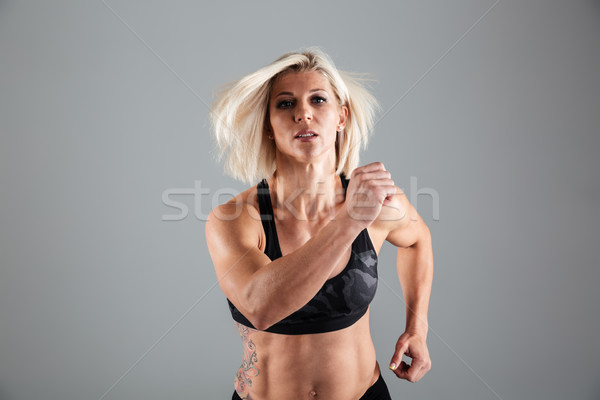 Portrait of a motivated adult female athlete running Stock photo © deandrobot