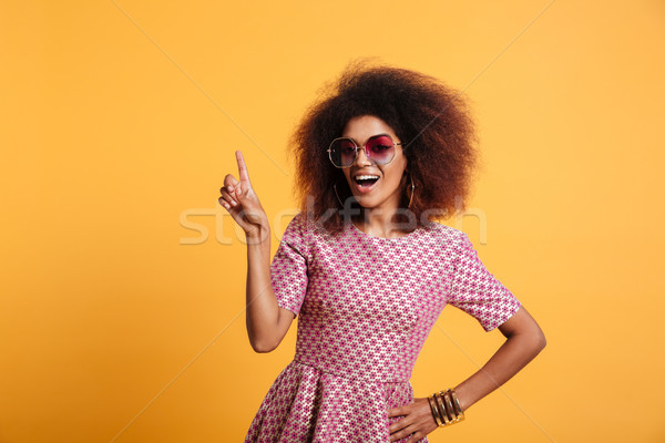 Pretty afro american retro woman with afro hairstyle pointing wi Stock photo © deandrobot