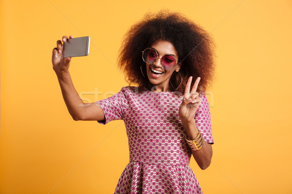 Portrait of a smiling afro american woman in retro style Stock photo © deandrobot