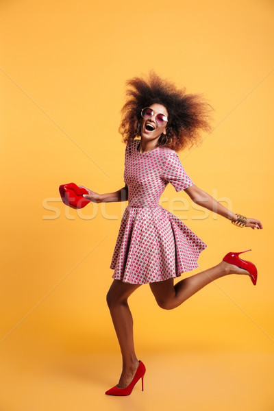 Full length portrait of an excited cheery afro american woman Stock photo © deandrobot