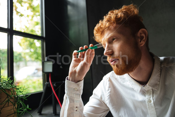 Close-up portrait of young concentrated readhead bearded man, ho Stock photo © deandrobot
