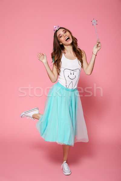 Full-length photo of cheerful adult princess with magic wand sta Stock photo © deandrobot
