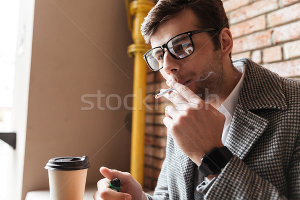 Side view of business man in eyeglasses sitting by table Stock photo © deandrobot