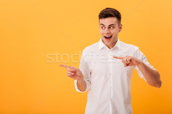 Picture of Happy man in white shirt pointing Stock photo © deandrobot