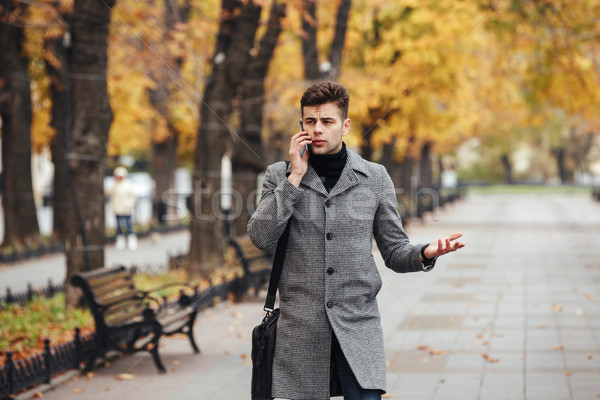 Picture of elegant male in coat with bag walking in city park, a Stock photo © deandrobot