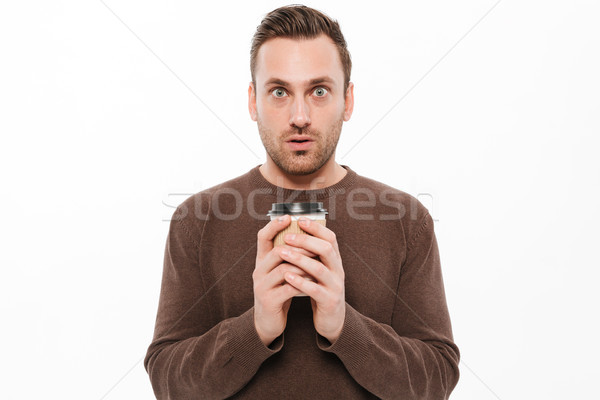 Shocked young man drinking coffee. Looking camera. Stock photo © deandrobot