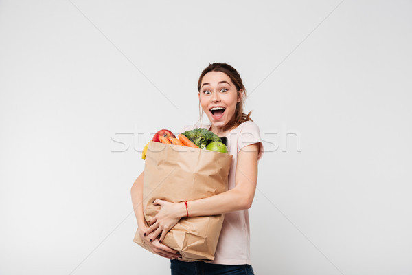 Portrait of an excited satisfied girl holding bag Stock photo © deandrobot