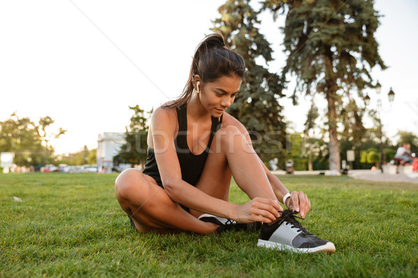 Portrait of young fitness girl tying her shoelaces Stock photo © deandrobot